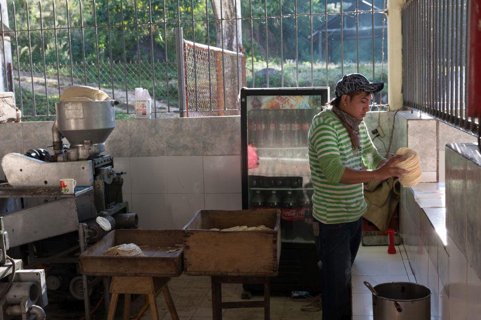 Tortillamaschine auf der Finca Hamburgo in Mexiko. Mitarbeiter hält einen Tortillastapel und gibt diese aus.